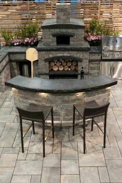 un'area barbecue scura in pietra e mattoni, con ripiani neri, una griglia e un forno per la pizza, oltre a una sala da pranzo
