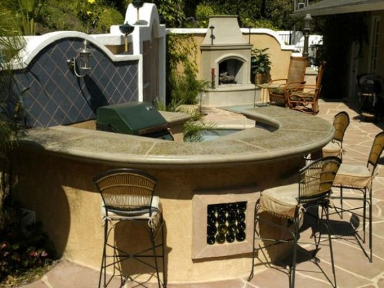 una confortevole zona pranzo in pietra, con un piano di lavoro in pietra e una griglia al suo interno più un focolare accanto