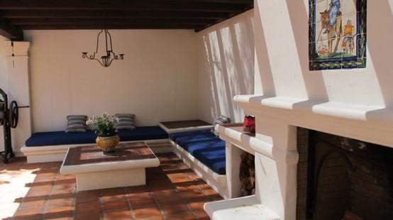 una zona relax esterna con seduta a L con rivestimento e tavolino basso