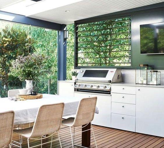 uno spazio da pranzo all'aperto semplice e moderno con un tavolo bianco e sedie in rattan più una griglia