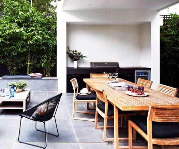 un elegante spazio da pranzo contemporaneo fatto con sedie in legno, un tavolo in legno e tappezzeria blakc, una griglia nera accanto ad essa