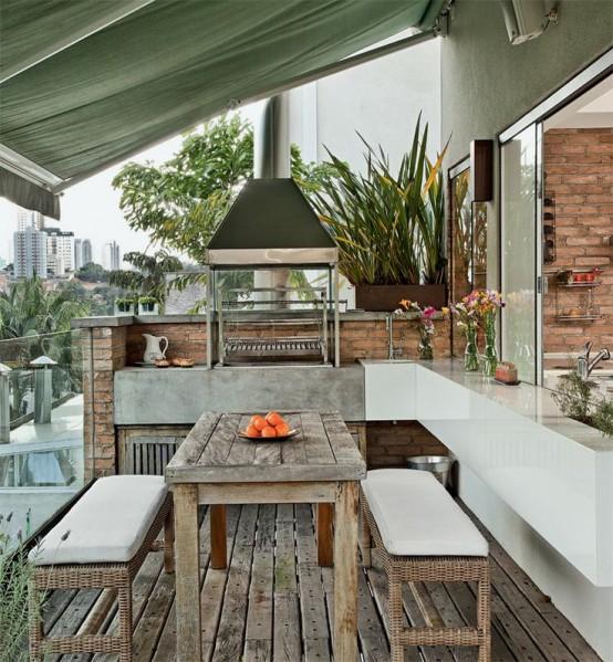 una zona barbecue all'aperto con una comoda zona pranzo e una zona cucina con grill sotto il tetto