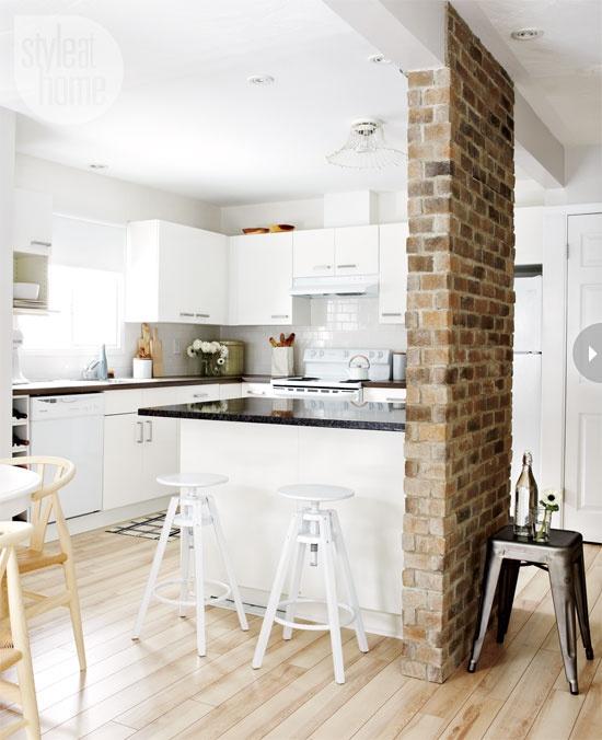 un pilastro di mattoni rossi separa la cucina dallo spazio successivo aggiungendo interesse e consistenza a entrambi