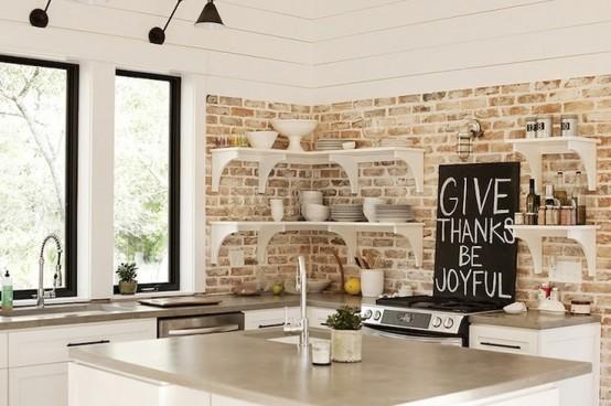 una cucina rustica neutra con mattoni imbiancati, mensole e armadi bianchi più molta luce naturale
