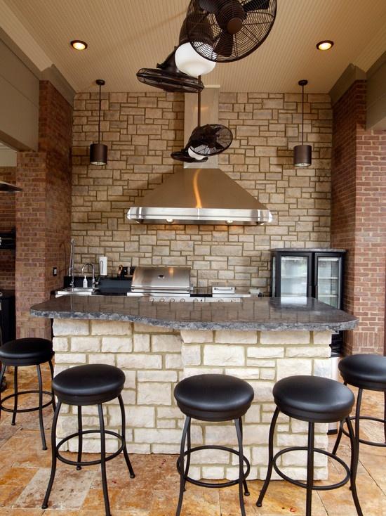 un muro in finta pietra e pilastri in mattoni rossi su ciascun lato rendono la cucina più audace e danno un tocco materico