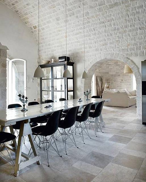 mattoni bianchi che vanno dalle pareti al soffitto ad arco sembrano audaci con mobili contemporanei in nero che creano un aspetto eclettico