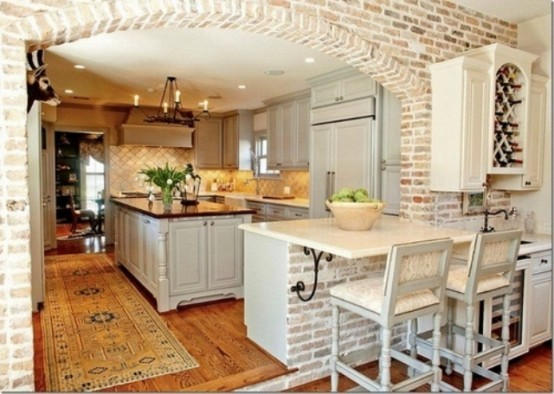 mattoni imbiancati e piastrelle neutre compongono una cucina elegante con un tocco rustico e vintage