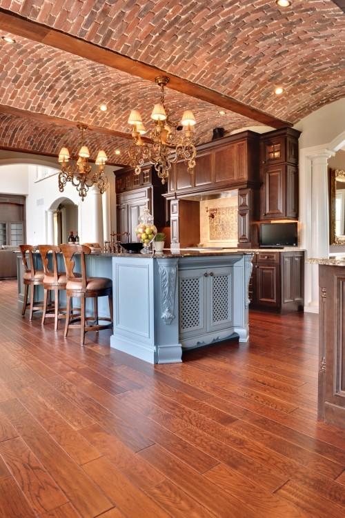 un soffitto ad arco in mattoni rossi con travi in legno e ricchi armadi in legno colorato creano uno spazio meraviglioso con un'elegante atmosfera vintage