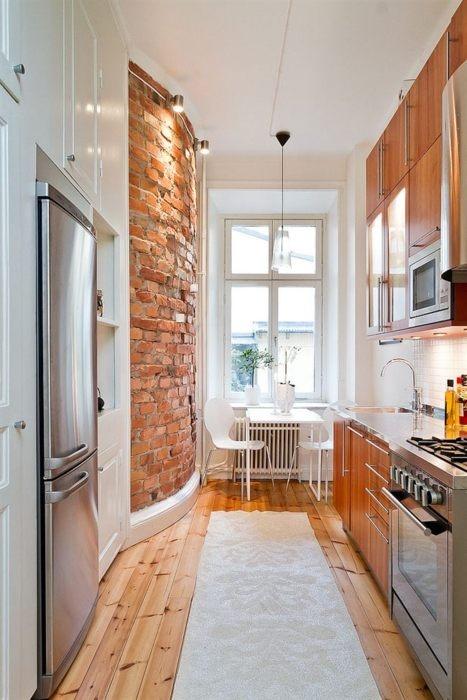 una cucina moderna realizzata in bianco con eleganti armadi in compensato che riecheggiano con il muro di mattoni rossi curvi