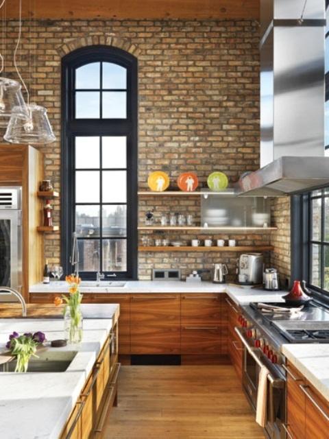 Pareti in mattoni a vista neutri abbinati a mobili in legno ambra per una cucina chic e luminosa con soffitti a doppia altezza