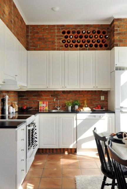 armadi bianchi vintage e mattoni rossi contrastano tra loro e aggiungono consistenza alla cucina
