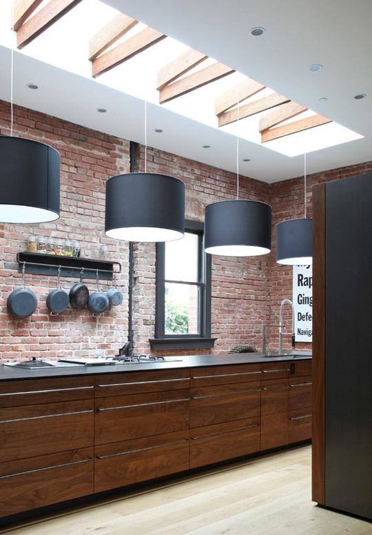 un muro di mattoni rossi e ricchi armadi in legno colorato per un'atmosfera maschile in cucina e lampade a sospensione nere su di esso