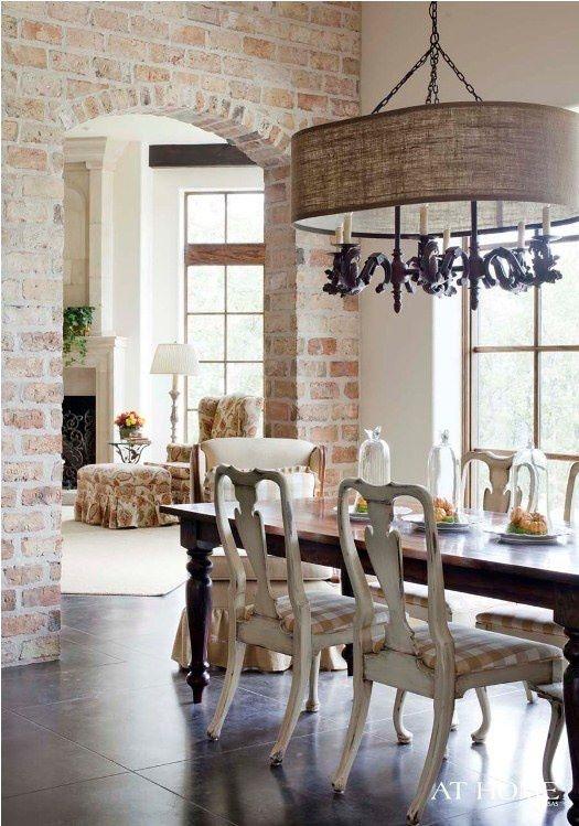 le pareti di mattoni rossi a vista nella sala da pranzo aggiungono consistenza e rendono questo spazio raffinato meno formale e più rilassato