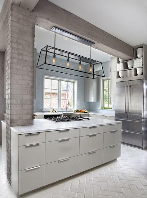 pareti in mattoni azzurri e un pilastro in mattoni tortora completano lo spazio aggiungendo sottili tocchi di colore alla cucina