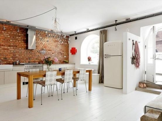 una cucina bianca brillante è arricchita da un muro di mattoni rossi che aggiunge interesse allo spazio e lo rende più pieno di colore