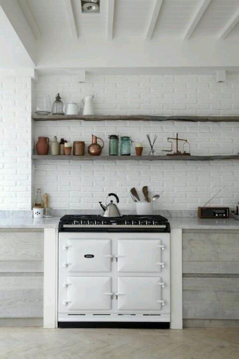 un muro di mattoni bianchi aggiunge consistenza allo spazio e allo stesso tempo si abbina all'arredamento neutro della cucina
