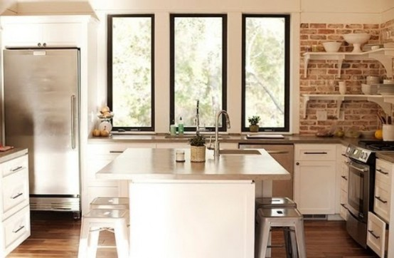 mattoni rossi, superfici metalliche lucide, semplici armadi bianchi compongono un'elegante cucina rustica e industriale