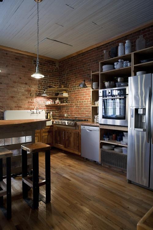 le pareti di mattoni rossi si abbinano al ricco legno tinto e aggiungono consistenza e interesse alla cucina
