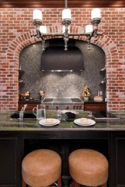 un muro di mattoni rossi contrasta le piastrelle grigie e un piano di lavoro in pietra verde e aggiunge colro allo spazio