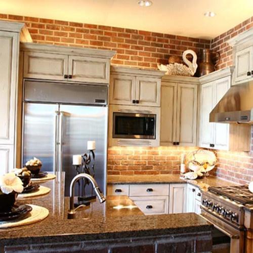 un muro di mattoni rossi abbinato a mobili vintage neutri compongono una cucina fresca di ispirazione vintage