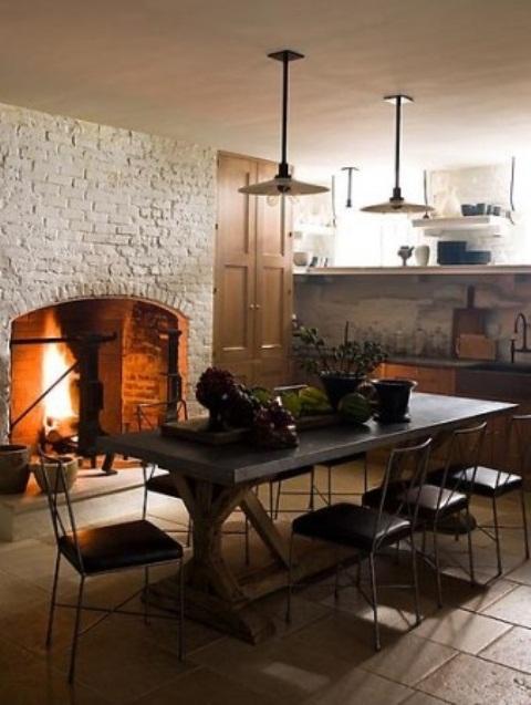 un grande camino rivestito di mattoni bianchi e un tavolo in cemento creano uno spazio fresco e aggiungono consistenza allo spazio