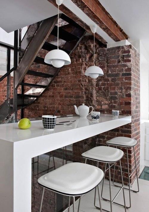 un muro di mattoni rossi a vista nella sala da pranzo porta consistenza, interesse e contrasta con i mobili bianchi lucidi