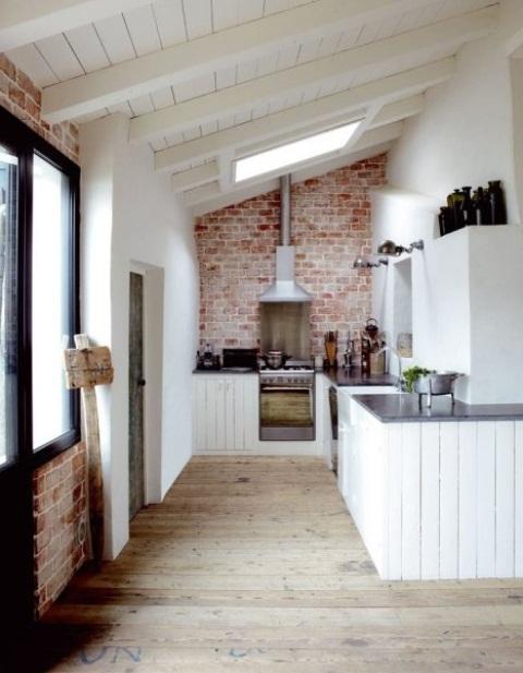 un muro di mattoni rossi e armadi in legno bianco portano consistenza e contrasto tra loro