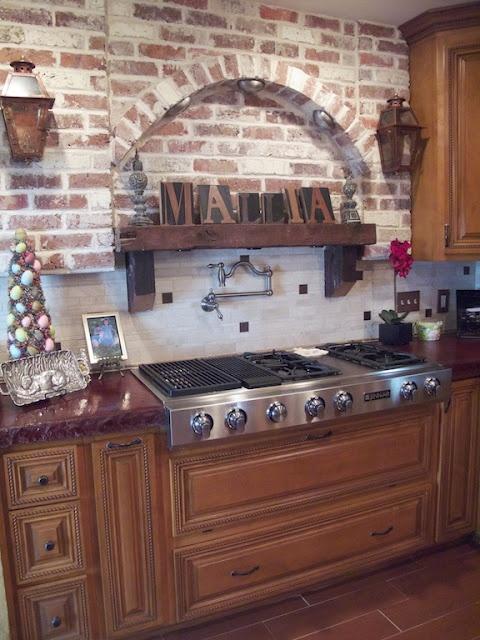 muri di mattoni rossi abbinati a ricchi mobili tradizionali colorati creano una cucina vintage accogliente e accogliente