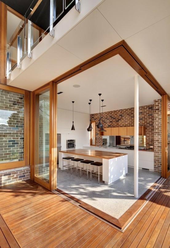un muro di mattoni rossi è una splendida dichiarazione nell'elegante spazio minimalista e aggiunge colore alla cucina