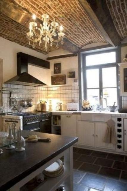 un soffitto in mattoni rossi con travi a vista è evidenziato con un lampadario di cristallo e contrasta la cucina neutra