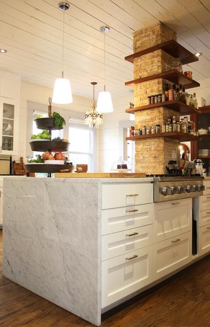 un pilastro in mattoni con ripiani in legno è un elemento decorativo accattivante che aggiunge consistenza e spazio di archiviazione alla cucina