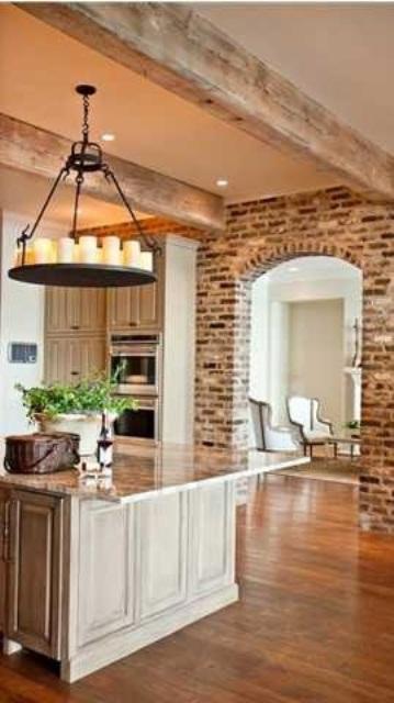 pareti in mattoni in difficoltà e travi in legno sul soffitto conferiscono consistenza e interesse alla cucina rendendola più rustica