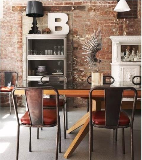 un muro di mattoni rossi in difficoltà nella zona pranzo e sedie in metallo si mescolano con mobili raffinati e contemporanei per un look unico