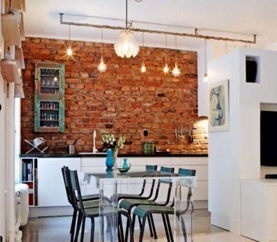 un muro di mattoni rossi spicca in un'elegante cucina bianca e aggiunge colore e consistenza allo spazio