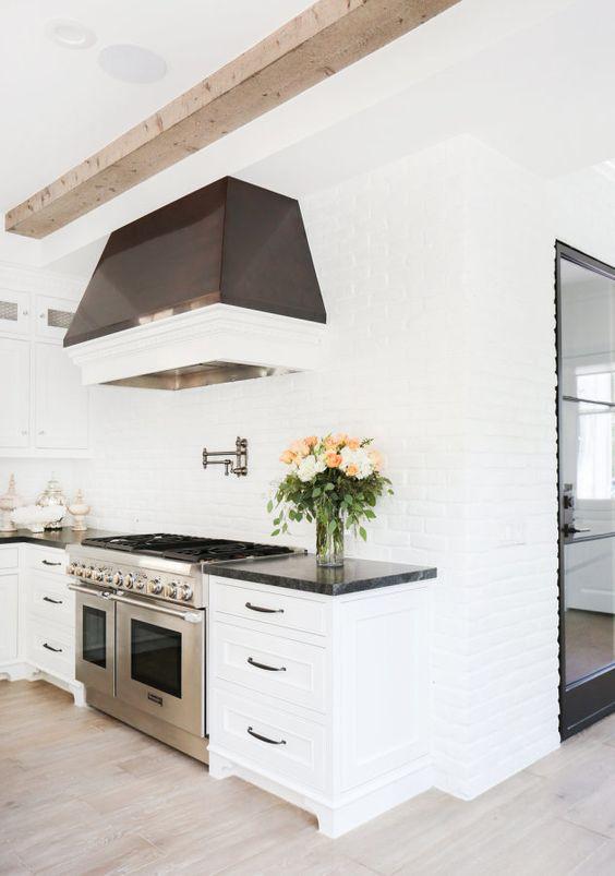 una cucina puramente bianca con pareti in mattoni bianchi e una cappa scura che risalta in uno spazio neutro