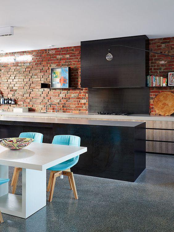 una cucina eclettica con eleganti armadi chiari e scuri, un muro di mattoni rossi e sedie turchesi luminose