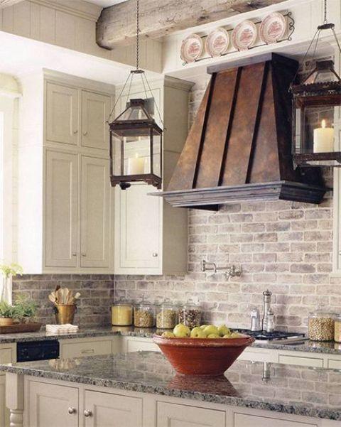 armadi bianchi, mattoni imbiancati, una cappa in metallo invecchiato compongono una cucina rustica chic ed elegante