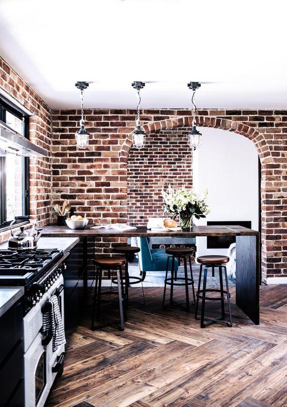 pareti in mattoni rossi audaci, pavimenti rivestiti di chevron colorati e ricchi mobili colorati per una cucina industriale incontra rustica