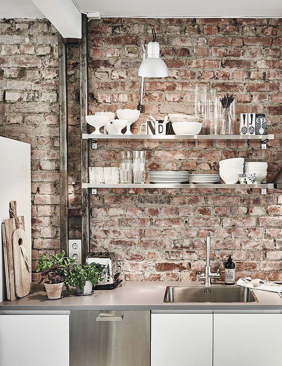 mobili da cucina in metallo bianco e lucido e pareti in mattoni rossi che rendono lo spazio più angosciato e rilassato