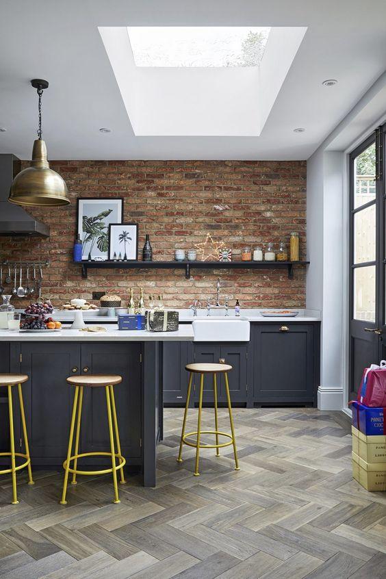 una cucina eclettica con armadi grigio grafite, ripiani bianchi e pareti rosse più tocchi in ottone