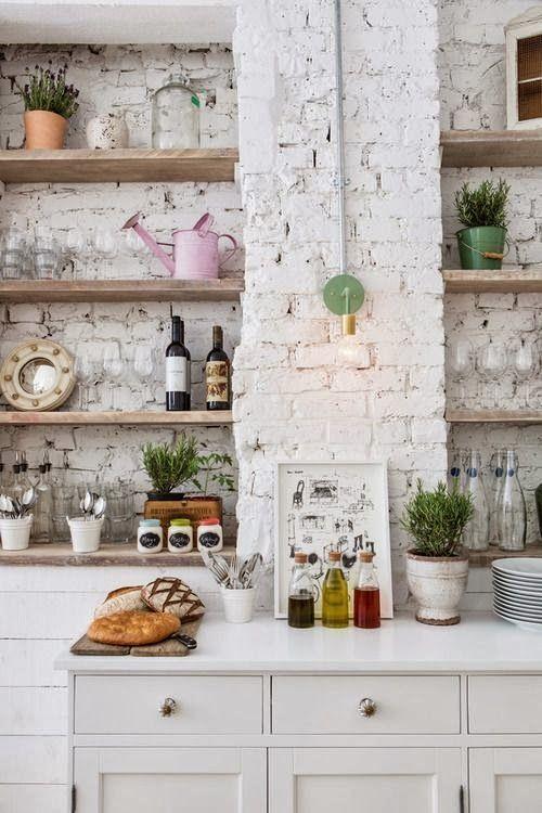 un'accogliente cucina scandinava con pareti in mattoni bianchi e mobili bianchi sembra chic