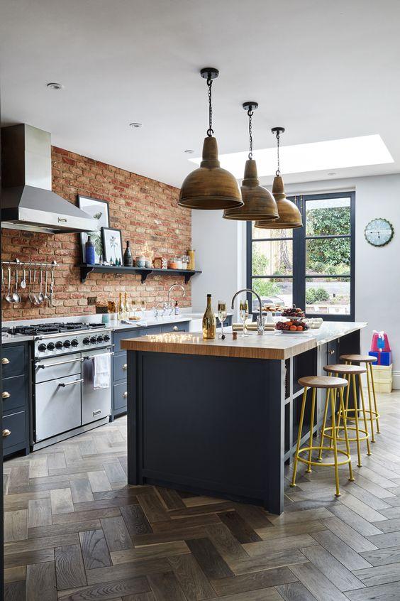 uno stile vittoriano incontra una cucina rustica con armadi grigio grafite, mattoni rossi e lampade a sospensione in metallo