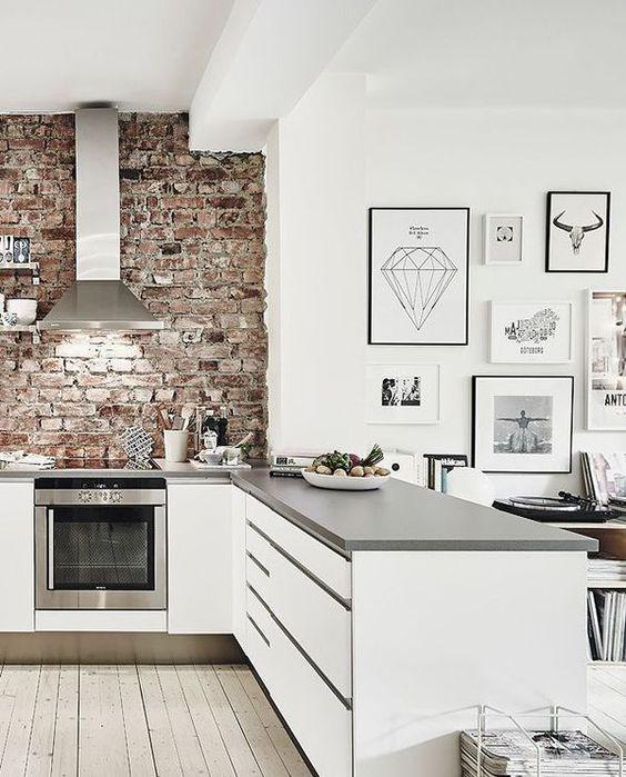 una cucina bianca con ripiani grigi è rinfrescata e ravvivata da un muro di mattoni rossi