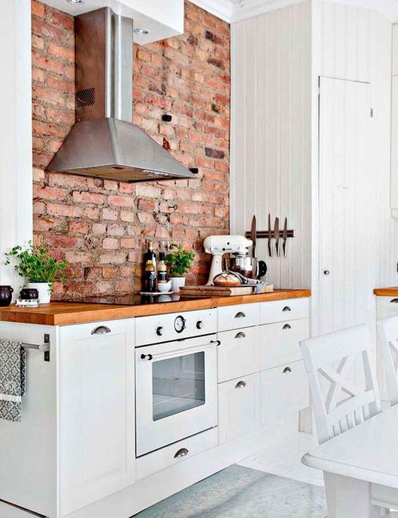 un'accogliente cucina moderna con mobili bianchi, ripiani colorati ricchi e un muro di mattoni rossi