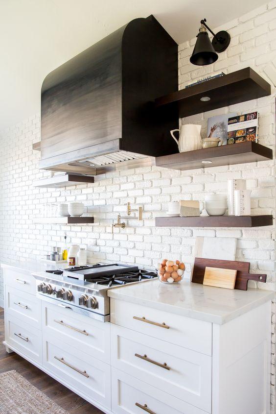 una cucina vintage con armadi bianchi, hardware in rame e un muro di mattoni finti bianchi che fa risaltare la cappa