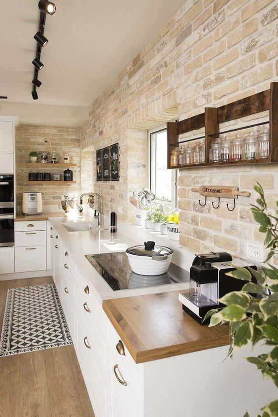 una moderna cucina da fattoria con mattoni imbiancati, armadi bianchi e piani di lavoro chic sembra molto accogliente