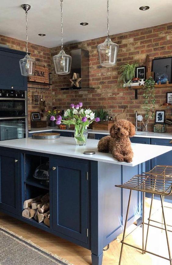 una cucina blu brillante con ripiani bianchi e lampade a sospensione in vetro è resa più audace con pareti di mattoni rossi