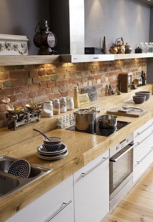 un backsplash in mattoni rossi contrasta i piani in legno neutri e gli armadi bianchi e rende la cucina accattivante