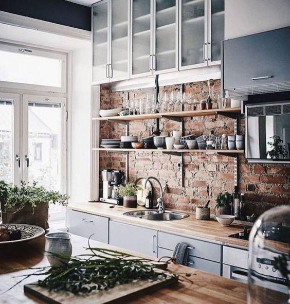 una cucina chic con armadi blu, ripiani di colore chiaro e un muro di mattoni rossi sembra molto rinfrescante