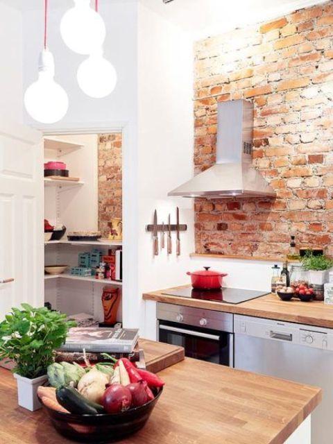 una moderna cucina da fattoria con mobili bianchi, elettrodomestici in metallo lucido e pareti di mattoni rossi